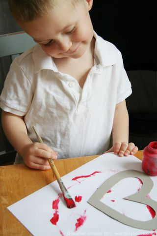 Boy-painting-heart-red