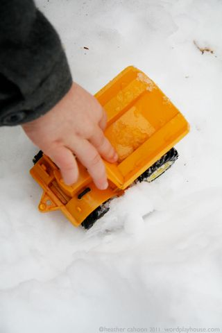 Child-playing-with-truck-in-snow